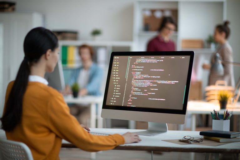 Moça frente a um Mac com um codigo de programação aberto. A imagem referência a automação.
