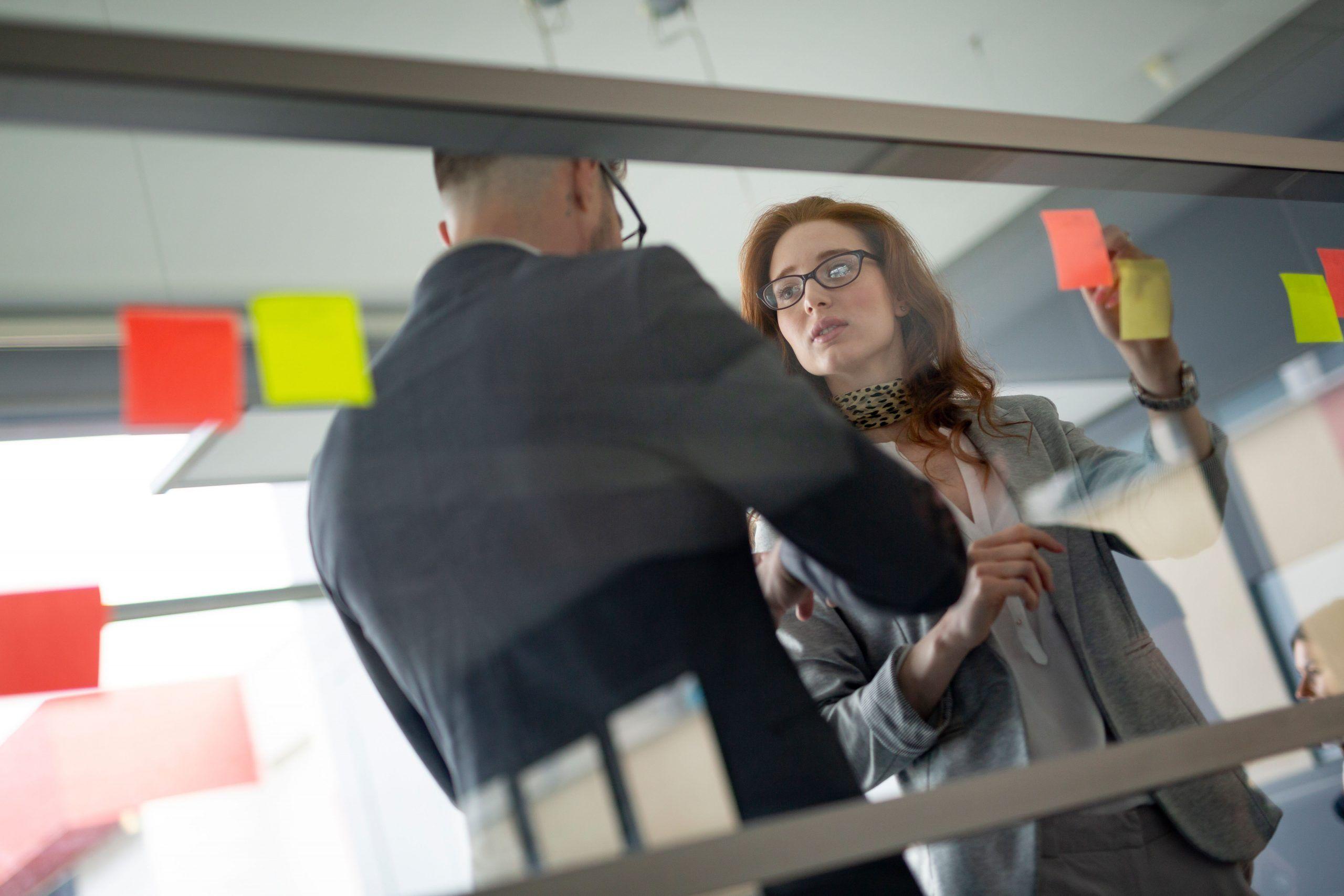 Dois gestores, um homem e uma mulher conversando sobre melhorias para a gestão de risco