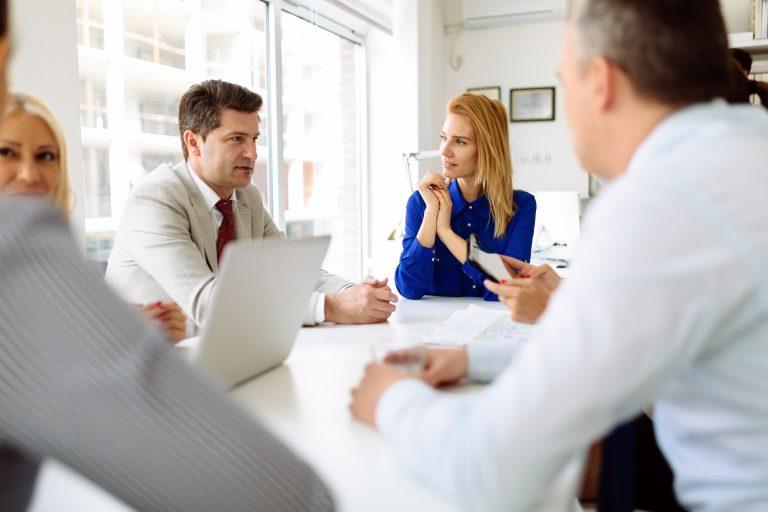 4 pessoas reunidas em volta de uma mesa conversando sobre os principais tipos de conciliações