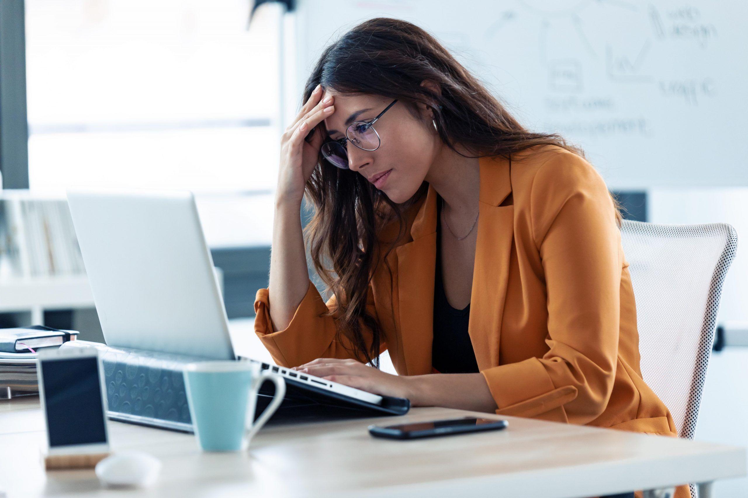 Mulher cm problemas na planilha, olhando para o computador com a mão na cabeça.