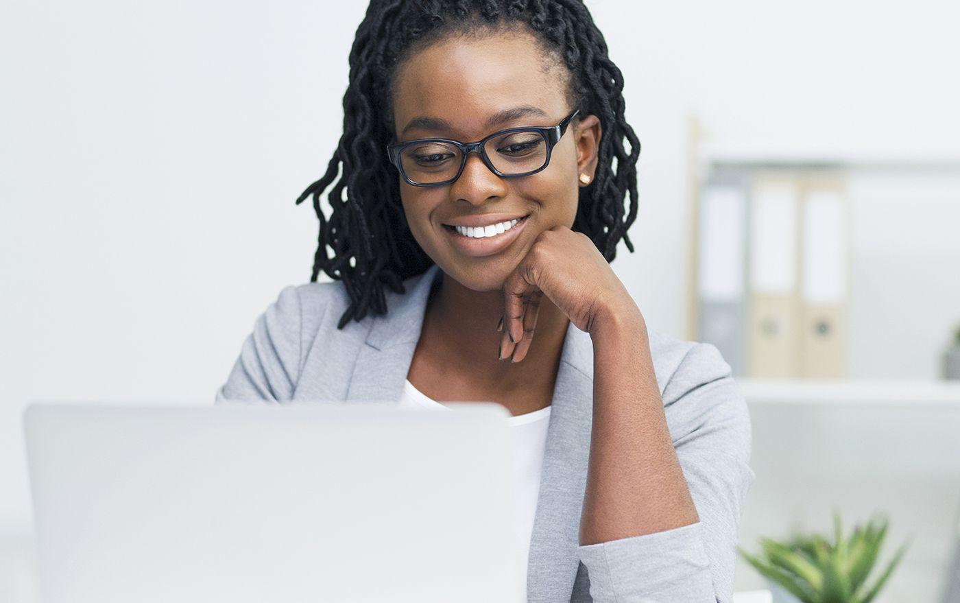 Mulher, negra, vestida de social, gerente do setor financeiro assistindo o Webinar Dattos sobre gestão da reconciliação