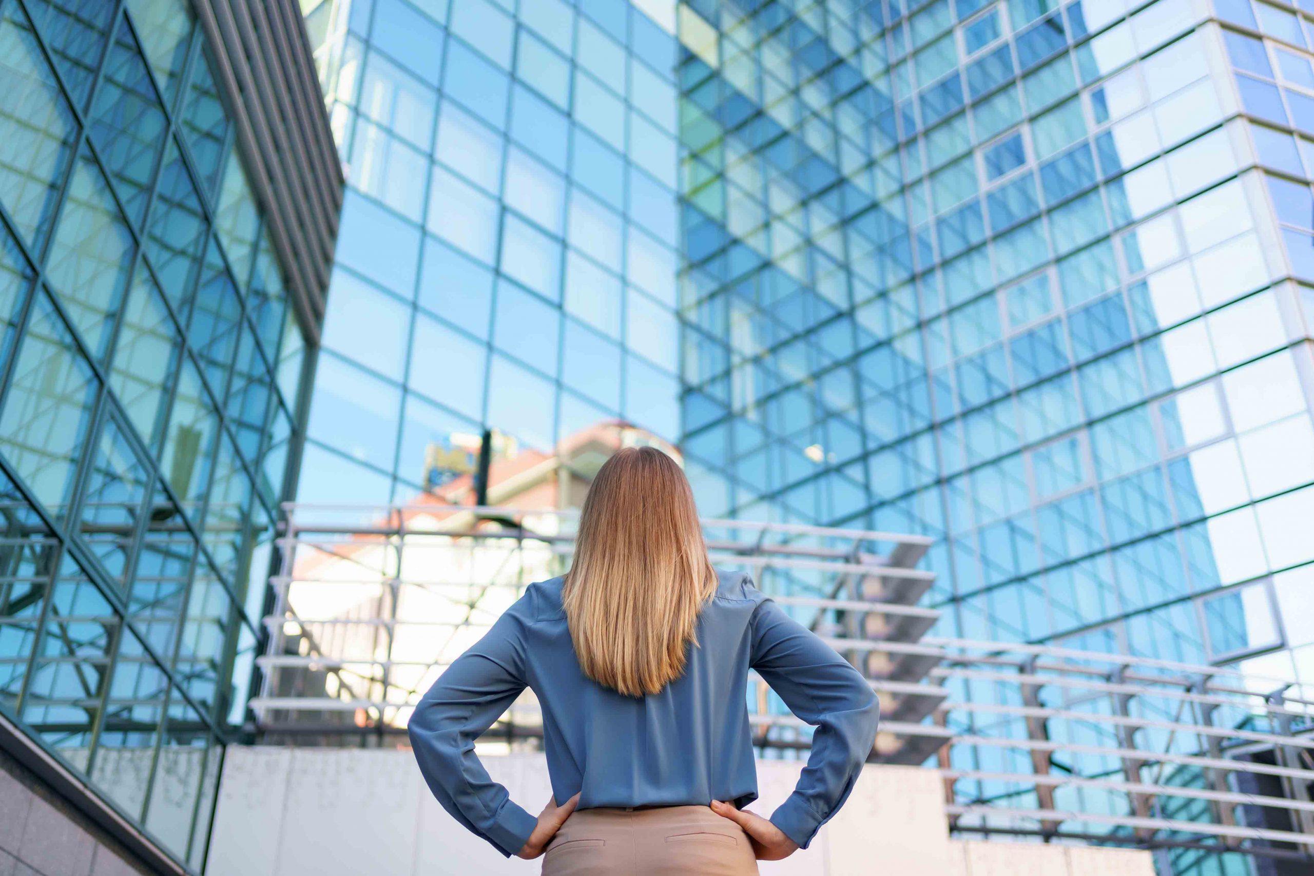 Mulher olhando grandes prédios empresariais, com diversas