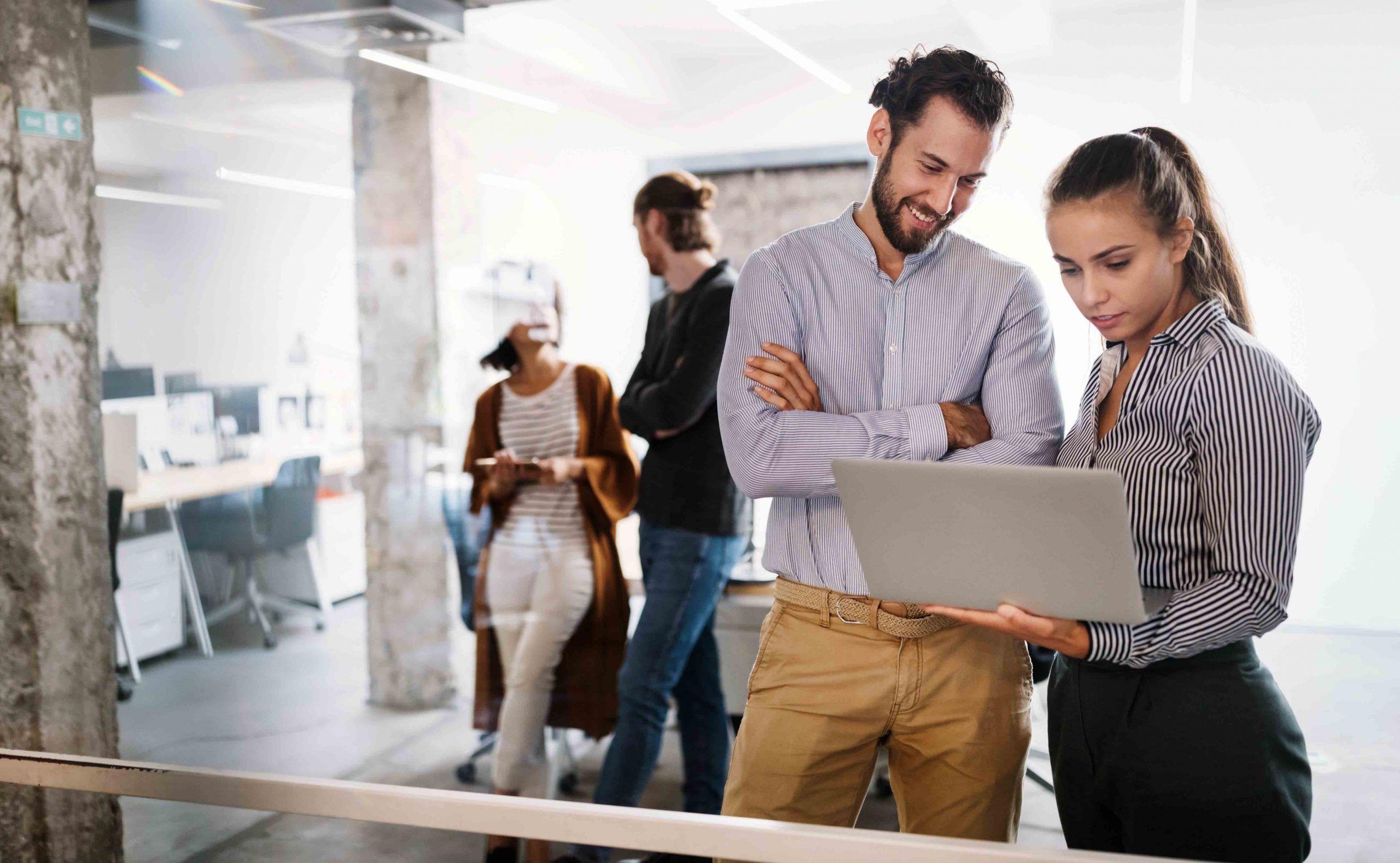 4 pessoas em um ambiente moderno, de start up, dois em segundo plano e 2 em primeiro plano com a face feliz e um notebook na mão da mulher.
