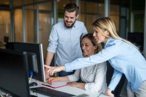 3 funcionários olhando um monitor com sorriso no rosto