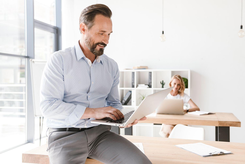 smiling man manager working on laptop